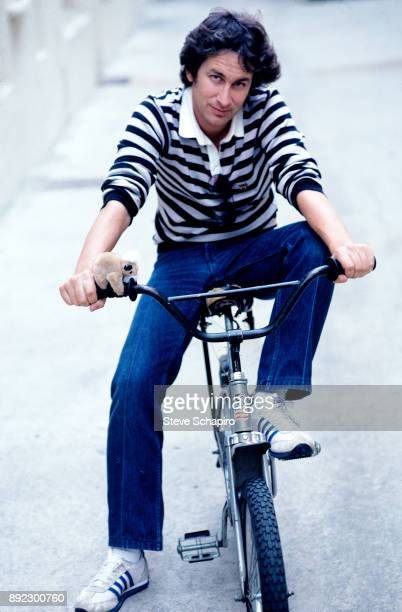 Portrait of American film director Steven Spielberg as he poses seated on a bicycle Los Angeles California 1981
