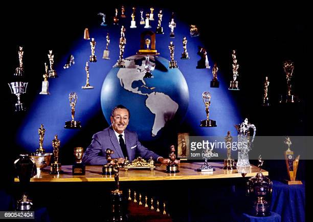 Portrait of American film producer and studio executive Walt Disney as he sits at his desk Burbank California January 1963 A number of trophies...