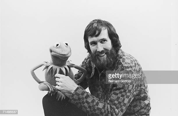 Portrait of American film televison director and puppeteer Jim Henson as he holds muppet Kermit the Frog late 1970s or early 1980s