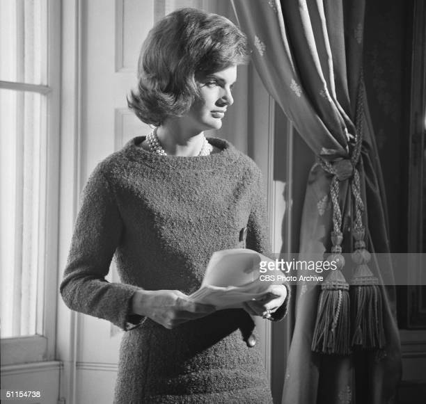 Portrait of American First Lady Jacqueline Kennedy in the White House Washington DC January 15 1962 She holds several papers as she stands in front...