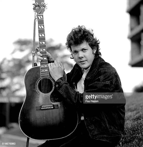 Portrait of American Folk and Pop musician Steve Forbert as he poses, with his guitar, outside the Park West Auditorium, Chicago, Illinois, October...