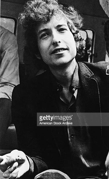 Portrait of American folk musician and songwriter Bob Dylan smiling and holding a cigarette early 1960s
