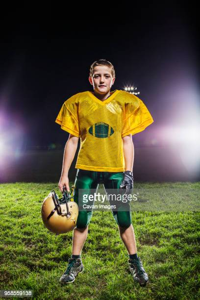 Portrait of American football player on field against sky