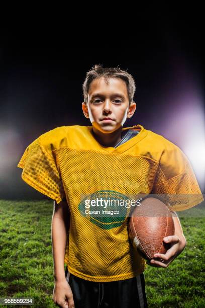 portrait of american football player with ball standing on field - american football uniform stock pictures, royalty-free photos & images