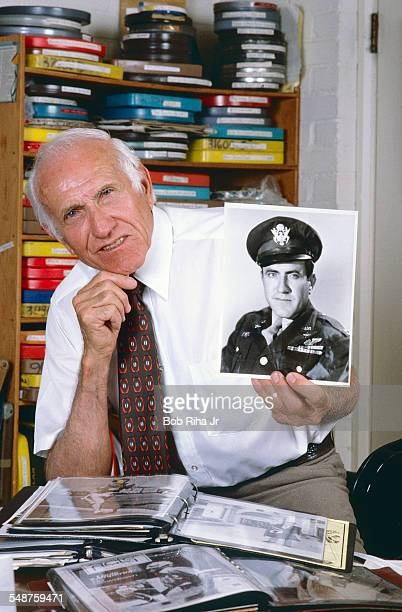 Portrait of American former bombardier Lt Louis Zamperini as he poses at home, a photo of himself during World War II in one hand, Los Angeles,...