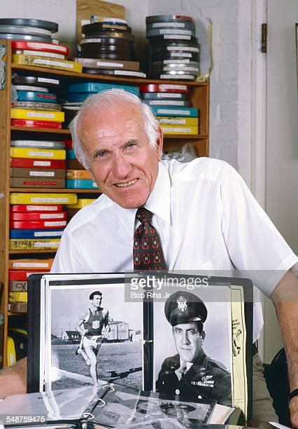 Portrait of American former bombardier Lt Louis Zamperini as he poses at home, Los Angeles, California, June 13, 1985. A photo album displays two...