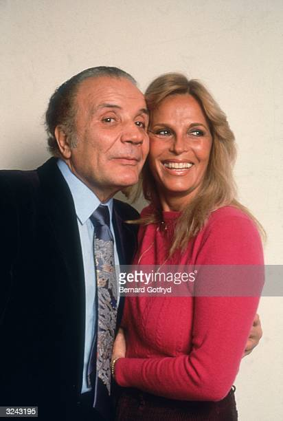 Portrait of American former professional boxer Jake LaMotta embracing his wife in front of a yellow backdrop