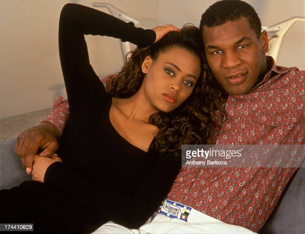 Portrait of American heavyweight boxer Mike Tyson and his wife actress Robin Givens as they pose together on a sofa in their new home Los Angeles...