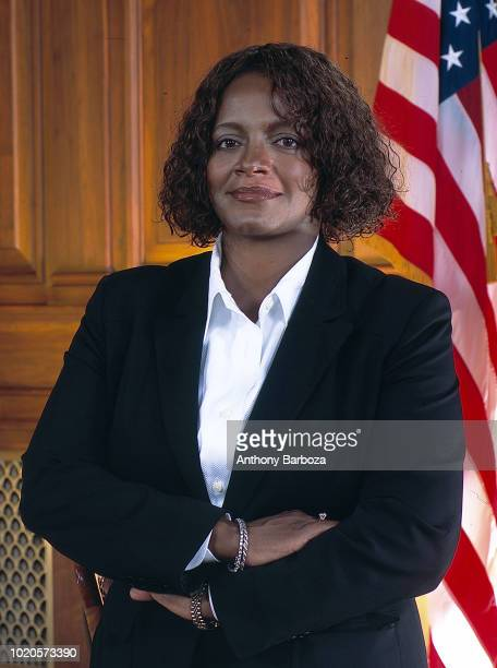 Portrait of American intellectual property attorney Sharon R Barner as she poses arms folded in front of an American flag Chicago Illinois 1990s