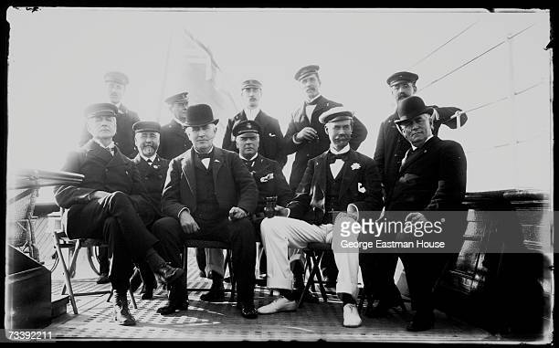 Portrait of American inventor Thomas Alva Edison and British buisnessman and sailing enthusiast Sir Thomas Johnstone Lipton as they sit with crew...