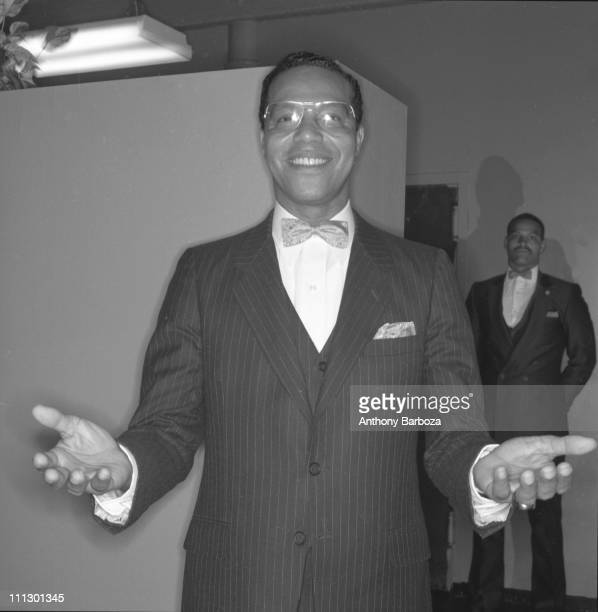 Portrait of American Islamic religious leader Louis Farrakhan standing with arms outstretched before him New York 1984