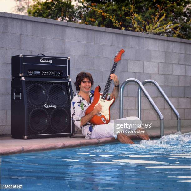 Portrait of American Jazz Fusion musician Ray Gomez, his guitar in hands, as he sits, poolside, with his feet in the water, Los Angeles, California,...
