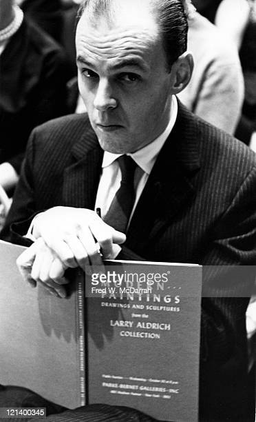 Portrait of American jazz musician and actor Conrad Janis as he holds an art catalogue from the Larry Aldrich collection New York New York October 28...
