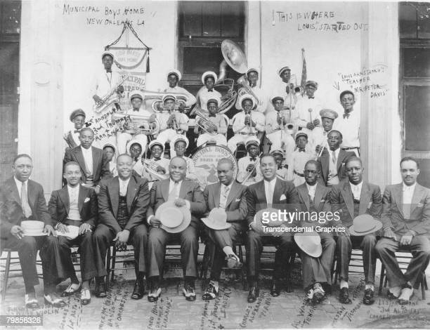 Portrait of American jazz musician Louis Armstrong and his band pose with members of the Municipal Boys' Home Brass Band and their teacher Peter...