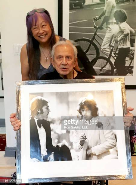 Portrait of American jewelry designer talk show host May Pang and American photographer Ron Galella as they pose together in the latter's home...