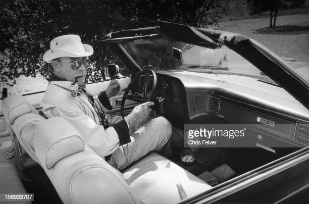 Portrait of American journalist and author Hunter S Thompson as he sits behind the wheel of a Pontiac Grand Ville convertible 1990 he has a...