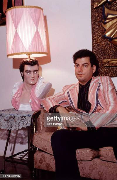 Portrait of American journalist Michael Musto as he poses on a coach, New York, New York, 1993. On a table beside him is an Elvis Presley lamp.