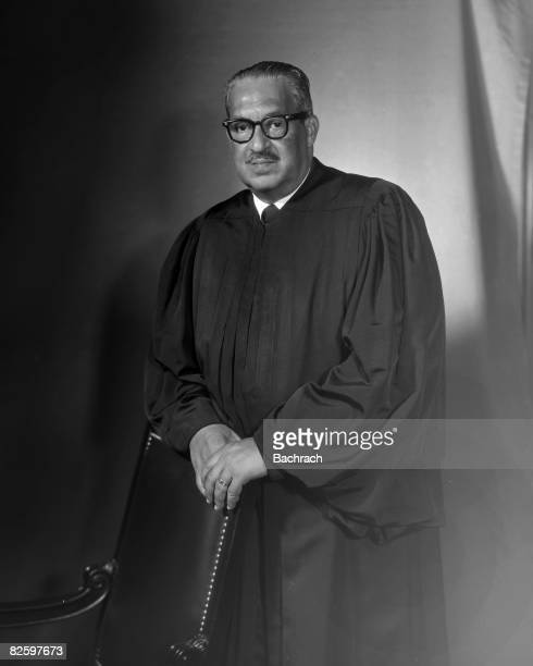 Portrait of American jurist Associate Justice of the United States Supreme Court Thurgood Marshall as he stands, his hands on the back of a chair,...