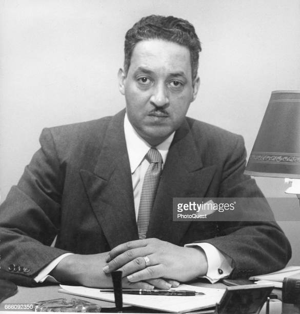 Portrait of American lawyer and special counsel of the National Association for the Advancement of Colored People Thurgood Marshall as he sits behind...