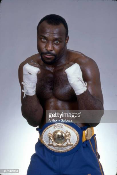 Portrait of American Light Heavyweight and Cruiserweight boxer Dwight Muhammad Qawi as he poses fists raised in shorts and a championship belt New...