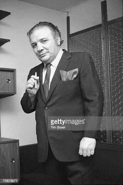 Portrait of American middleweight boxing legend Jake LaMotta as he stands and holds a cigar 1970