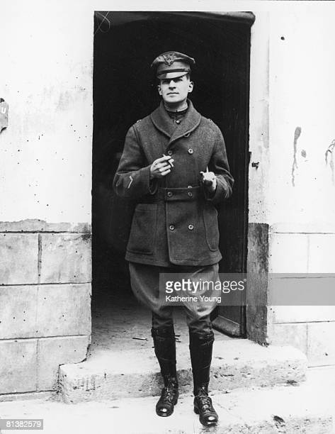 Portrait of American military commander Douglas MacArthur as he stands in a doorway a cigaratte in one hand and a swatter under his arm late 1910s