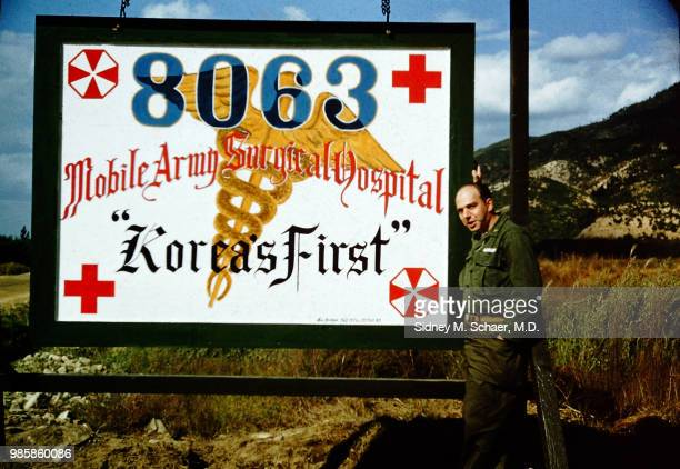 Portrait of American military surgeon Captain Sidney Schaer as he poses with the large sign for his unit the 8063rd MASH which also reads 'Korea's...