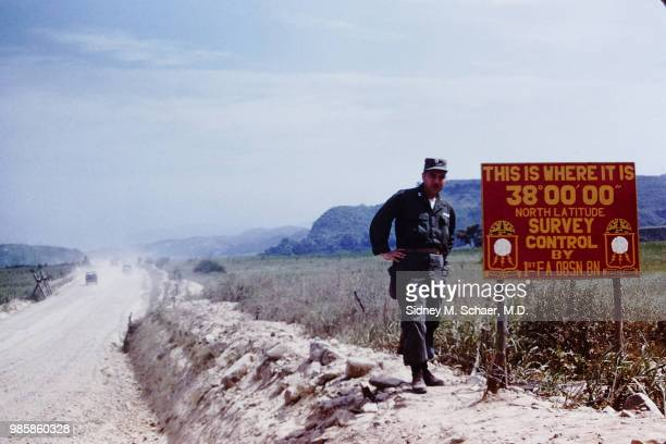 Portrait of American military surgeon Captain Sidney Schaer of the 8063rd MASH as he poses hands on his hips beside a sign indicating the 38th...