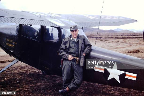 Portrait of American military surgeon Captain Sidney Schaer of the 8063rd MASH as he leans against the fuselage of a Cessna L19 Bird Dog observation...