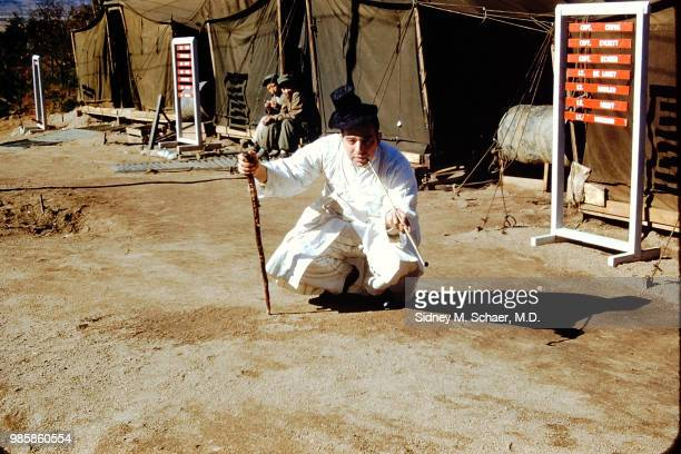 Portrait of American military surgeon Captain Sidney Schaer of the 8063rd MASH dressed in traditional Korean clothing as he smokes a long pipe while...