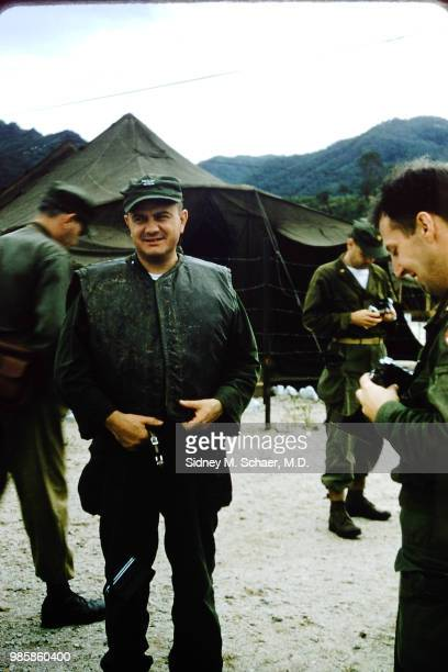 Portrait of American military surgeon Lieutenant Colonel John M Salyer in an armored vest as he stands among unidentified others at the 8063rd MASH...