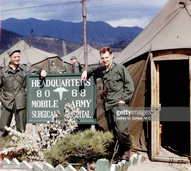 Portrait of American military surgeons Richard Warren and Roger Wilcox as they pose beside the sign outside the 8063rd MASH camp headquarters South...
