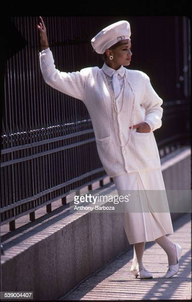 Portrait of American model actress and singer Vanessa L Williams dressed in an allwhite ensemble as she poses beside a metal fence New York 1980s