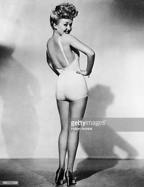 Portrait of American model and actress Betty Grable as she stands in high heels and a onepiece bathing suit and looks over her shoulder one hand on...
