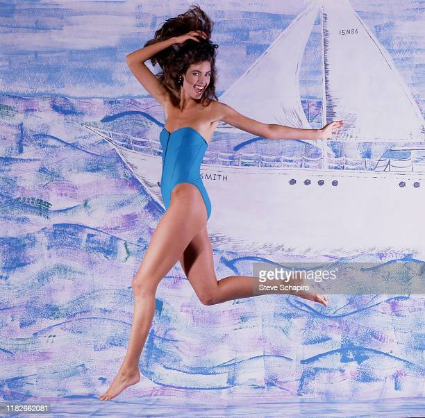 Portrait of American model and actress Carol Alt, in a one-piece swimsuit, as she poses against a blue background , Los Angeles, California, 1993.
