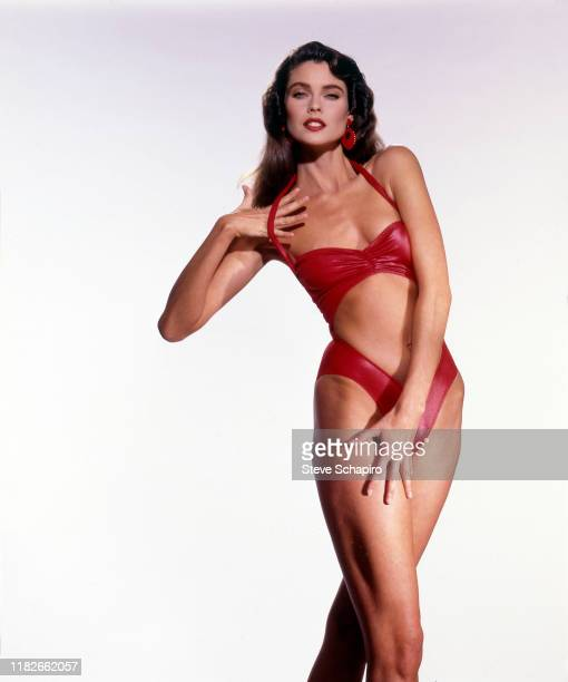 Portrait of American model and actress Carol Alt in a red onepiece swimsuit as she poses against a white background Los Angeles California 1993
