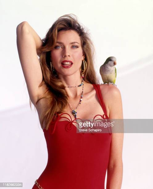 Portrait of American model and actress Carol Alt, in a red outfit, as she poses with a parakeet perched on her shoulder during a photo shoot for her...