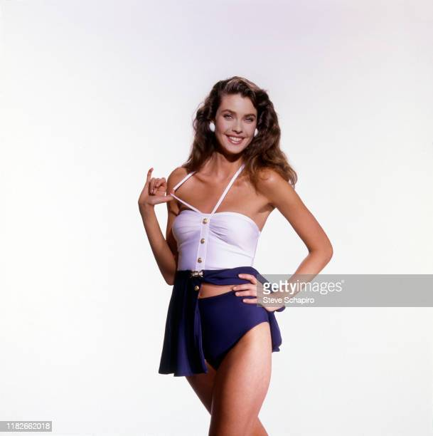 Portrait of American model and actress Carol Alt in a twopiece swimsuit with a wrap skirt as she poses against a white background Los Angeles...