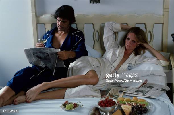 Portrait of American model and actress Cheryl Tiegs and her husband film director Stan Dragoti lie in bed with newspapers and food from room service...