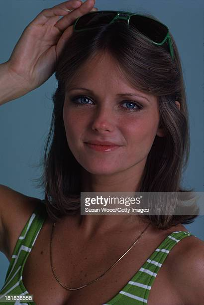 Portrait of American model and actress Cheryl Tiegs as she poses dressed in a green and white stripped bikini top and green rimmed sunglasses 1974...