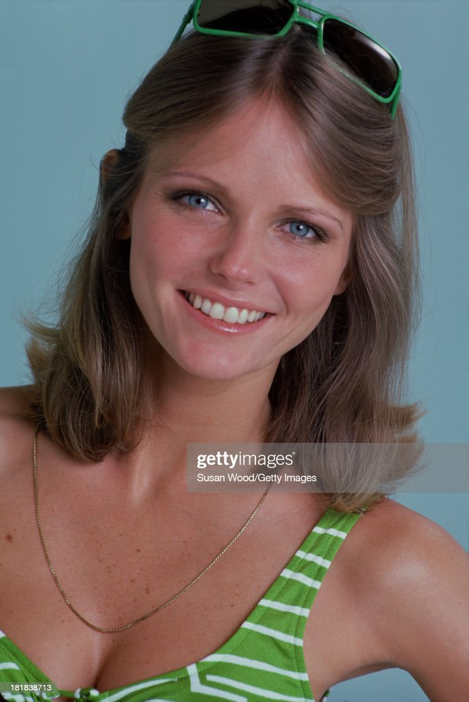 Portrait of American model and actress Cheryl Tiegs as she poses, dressed in a green and white stripped bikini top and green rimmed sunglasses, 1974. The photo was taken as part of a cover shoot for the May 1974 issue of Women's Own magazine.