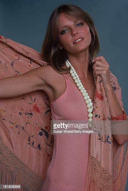 Portrait of American model and actress Cheryl Tiegs as she poses dressed in a rosecolored sleeveless dress a pink rosepatterned fringed shawl and...