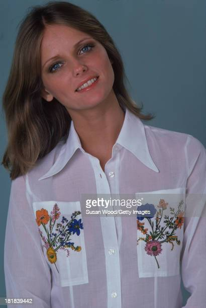 Portrait of American model and actress Cheryl Tiegs as she poses dressed in a white shirt with floral embroidery on the pockets 1974 The photo was...
