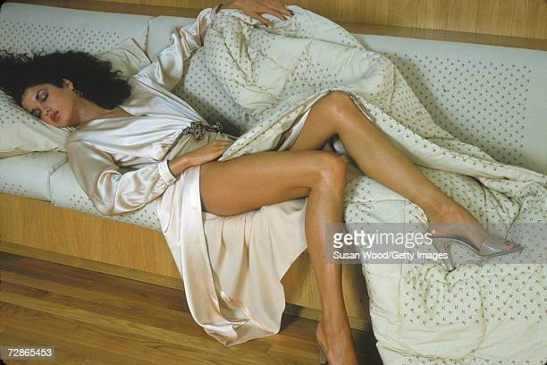 Portrait of American model Janice Dickerson as she lies, eyes closed, on a sofa, dressed in a silk gown and partially covered by a comforter,...