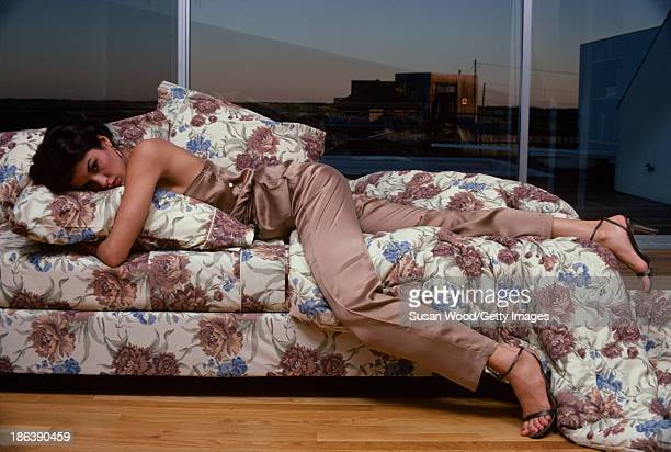 Portrait of American model Janice Dickinson dressed in a silk champagnecolored jumpsuit as she lies on a bed in front of a picture window Amagansett...