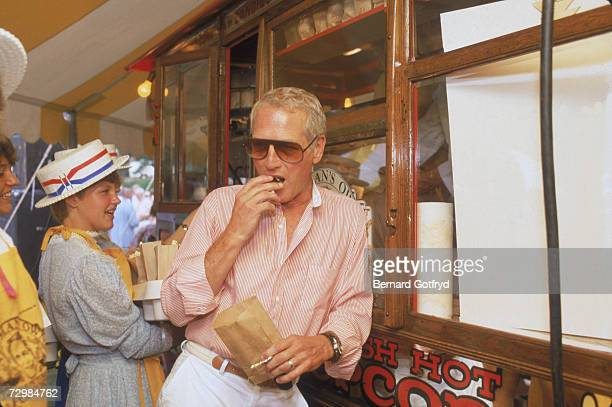 Portrait of American movie actior and philanthropist Paul Newman as he eats from a bag of popcorn and leans against a popcorn stand that stocks his...