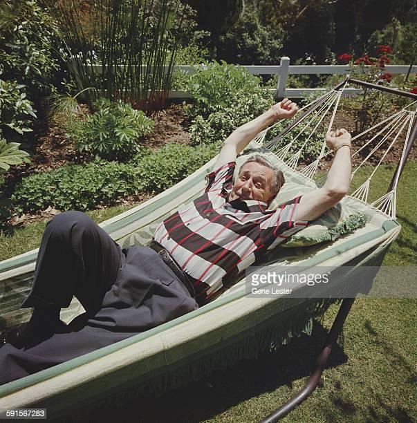 Portrait of American movie producer artist and animator Walt Disney as he lies in a hammock 1950s