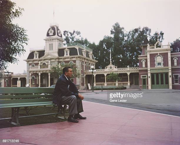 Portrait of American movie producer artist and animator Walt Disney as he sits on a bench in his Disneyland amusement park Anaheim California 1950s