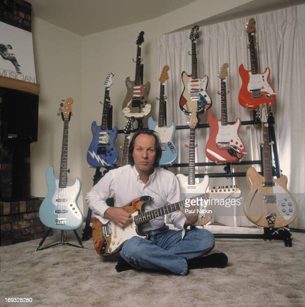 Portrait of American musician Adrian Belew as he poses at home in front of a rack of various guitars Lake Geneva Wisconsin December 15 1986