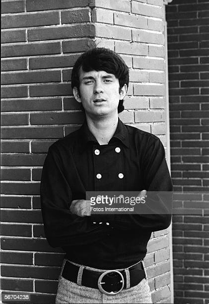 Portrait of American musician and actor Michael Nesmith in a double breated shirt of the popular music and television group the Monkees as he lean...
